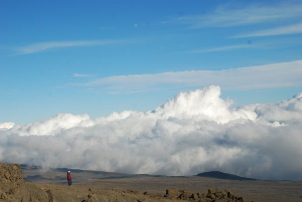 A porter stands overlooking the Saddle with a bank of clouds being held below it