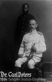 Dr Carl Peter, seated and dressed in a white uniform, with a local uniformed manservant standing behind him