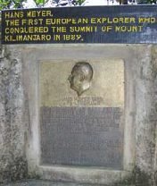 Memorial to Hans Meyer, the first man at the summit of Kilimanjaro. The memorial has a profile of Meyer in relief, above which is written in yellow capitals