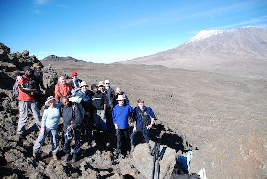 Group of Kilimanjaro climbers with the desert of the Saddle behind them and snowy Kibo in the distance