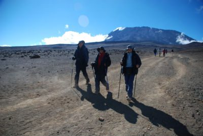 Three trekkers, with several others in the distance behind them, strolling across the Saddle of Kilimanjaro with Kibo in the background