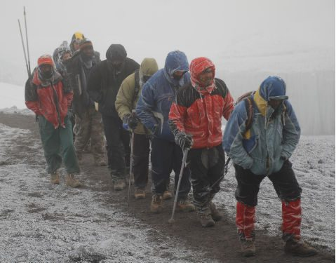 A group of six trekkers and three guides walk up towards Kilimanjaro's summit, each covered in a frosting of snow. It looks very cold.
