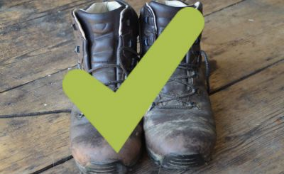 Pair of old trekking boots with green tick on top to show that they are suitable for Kilimanjaro